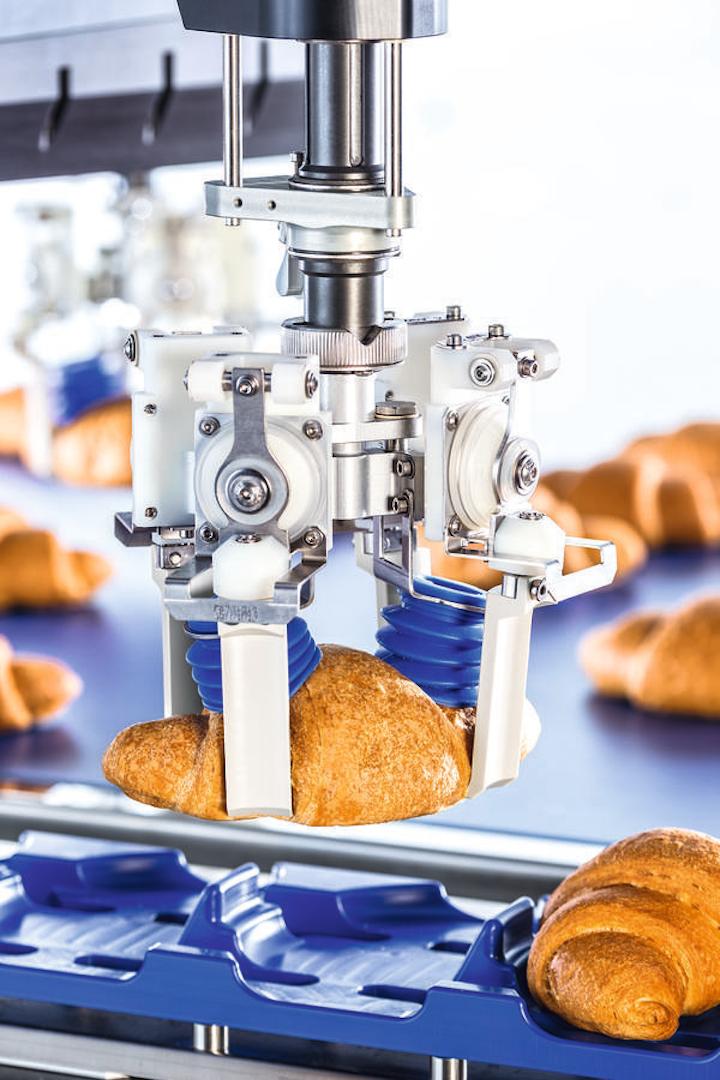 Un robot de dos ejes suavemente levanta los croissants llenos de un módulo de transporte y los coloca de nuevo en una cinta transportadora.