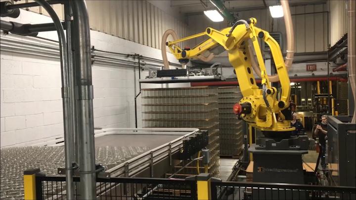 A una velocidad de 2.5 capas por minuto, el robot recoge una capa llena de frascos de un palé y la coloca sobre el área de alimentación de la línea de llenado.